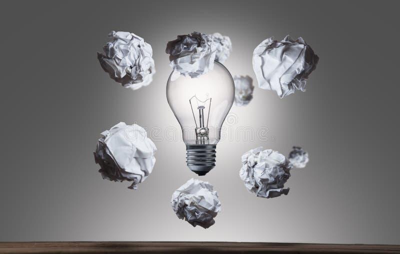 Скомканные бумажные шарики летая электрическая лампочка arround стоковая фотография