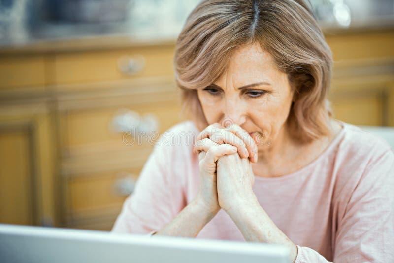 Сконцентрированная женщина вытаращится задумчиво в ноутбуке стоковые фотографии rf