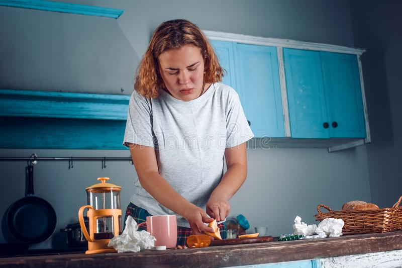 Сконцентрированная женщина отрезает лимон на разделочной доске в кухне стоковые фотографии rf