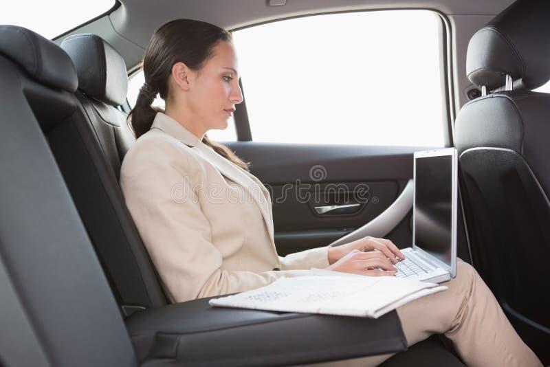 Сконцентрированная коммерсантка работая в заднем сиденье стоковая фотография rf