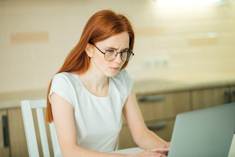 Сконцентрированная коммерсантка redhead работая на компьтер-книжке в ярком современном офисе стоковые изображения rf