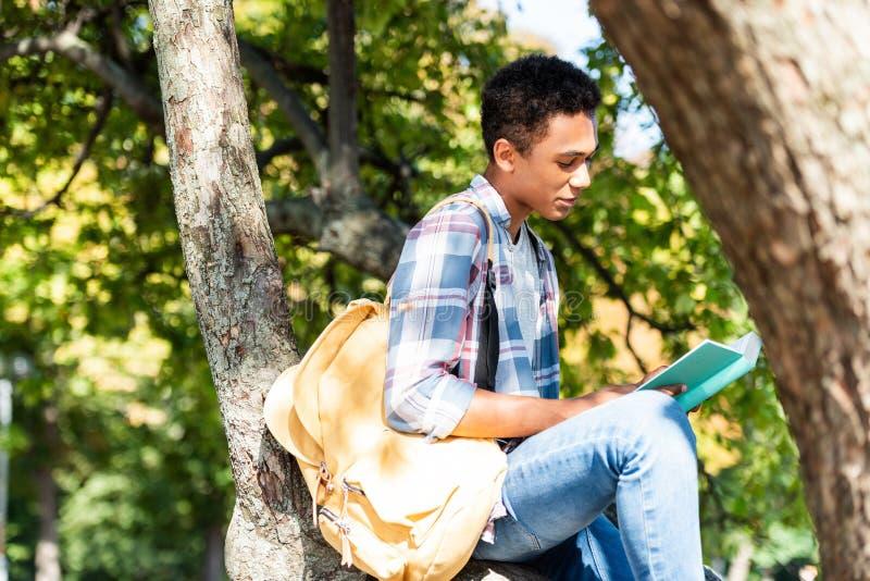 сконцентрированная предназначенная для подростков книга чтения студента пока сидящ стоковое фото rf