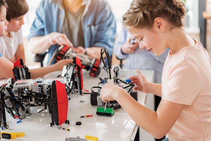 Сконцентрированная усмехаясь девушка создавая техническую игрушку стоковая фотография rf