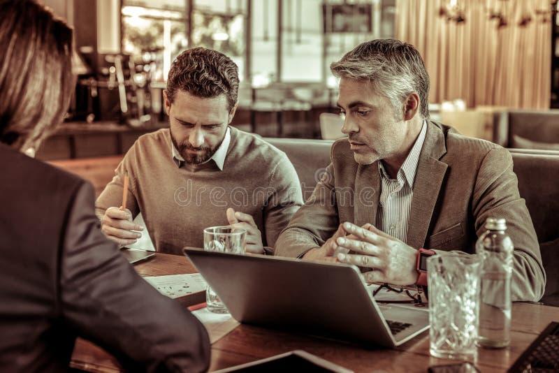 Сконцентрированное бородатое деловое соглашение чтения мужск человека стоковые фотографии rf