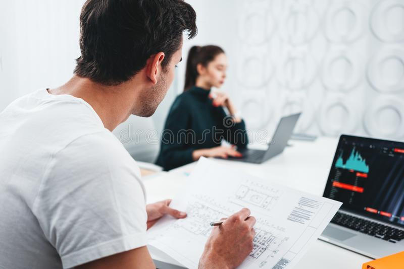 Сконцентрированные дизайнеры здания работая с планом и компьютером чертежа пока сидящ таблицей на офисе студии стоковое фото rf