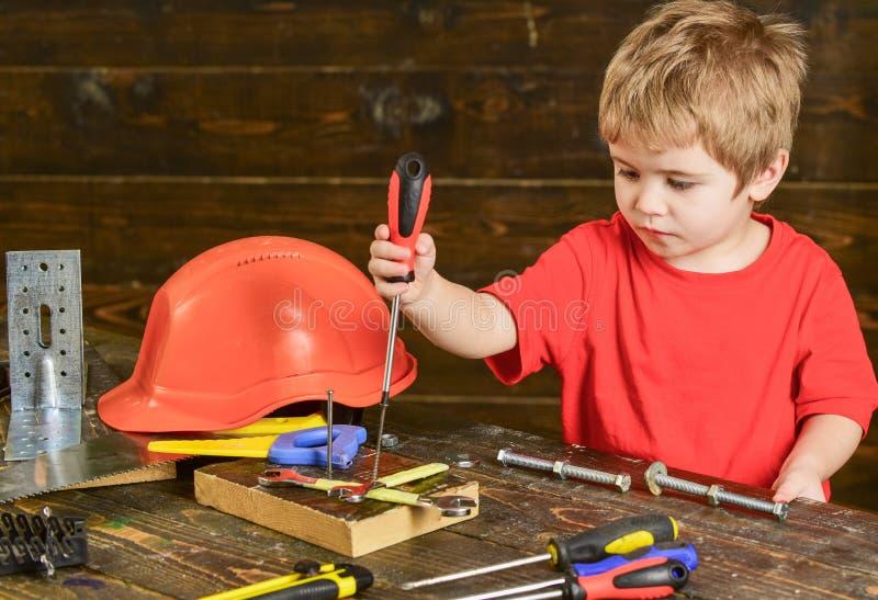 Сконцентрированные зажимные винты ребенк к деревянной доске Белокурый мальчик играя с комплектом инструментов Preschooler уча нов стоковое фото