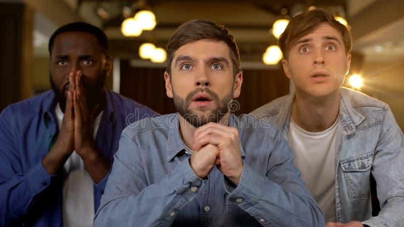 Сконцентрированные парни наблюдая игру, тревожащся о результатах спички, ждать цель стоковое фото