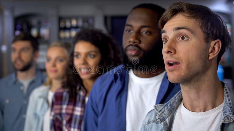 Сконцентрированные сторонники внимательно смотря ТВ, ждать результаты состязания стоковое фото rf