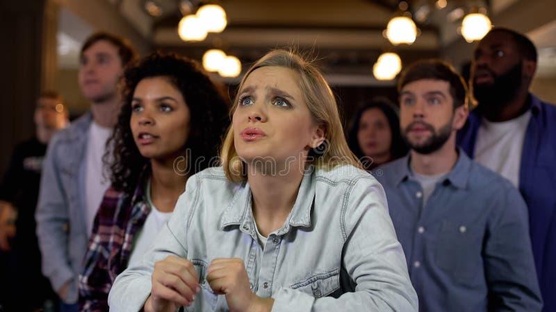 Сконцентрированные сторонники команды ждать цель, развлечения болельщиков, утеху стоковое изображение rf