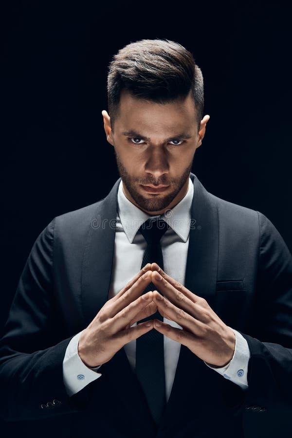 Сконцентрированный бизнесмен делает зловещие планы стоковые фото
