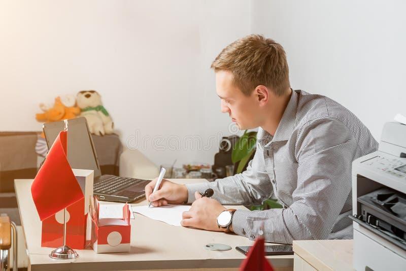 Сконцентрированный бизнесмен принимая примечания перед ноутбуком в его современном офисе стоковое фото rf