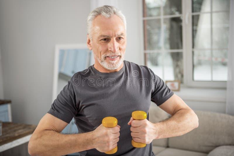 Сконцентрированный бородатый мужчина держа гантели стоковые изображения rf