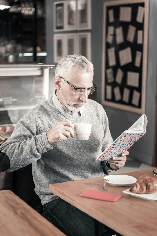 Сконцентрированный бородатый человек читая стихотворения в кафе стоковая фотография