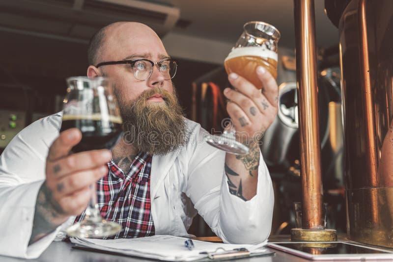 Сконцентрированный бородатый человек стоя в доме brew стоковые изображения rf