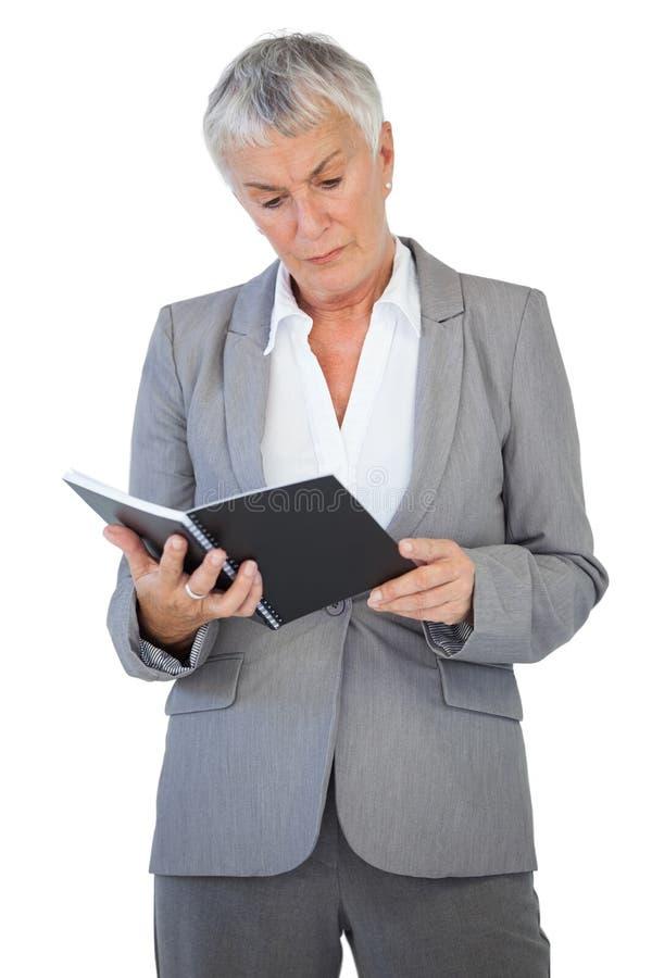 Сконцентрированный блокнот чтения коммерсантки стоковое фото