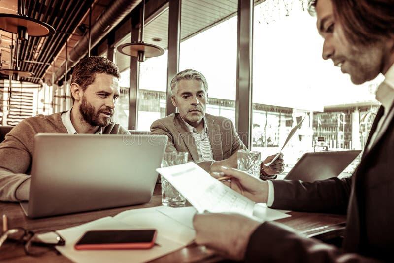 Сконцентрированный достигший возраста мужск человек слушая его коллегу стоковые изображения rf