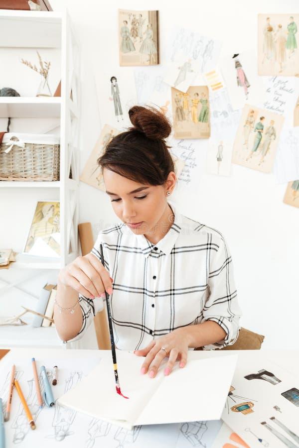 Сконцентрированный детенышами иллюстратор моды женщины стоковые фотографии rf