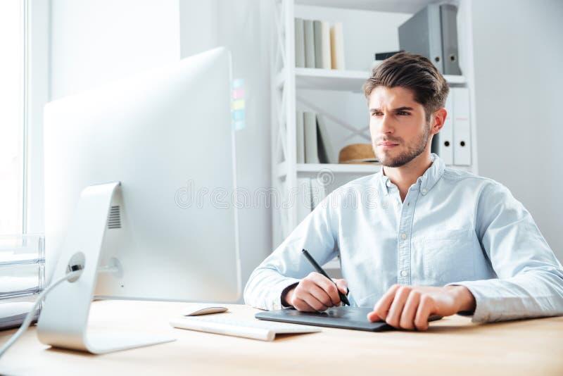 Сконцентрированный дизайнер молодого человека работая с компьютером и графической таблеткой стоковые фотографии rf