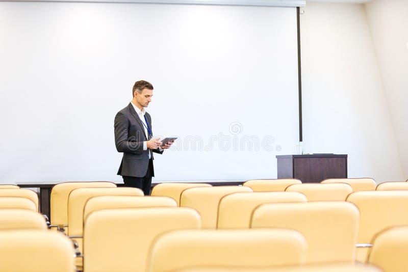 Сконцентрированный диктор повторяя речь с таблеткой в пустом зале заседаний правления стоковое изображение