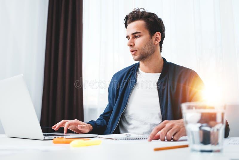 Сконцентрированный менеджер работая на ноутбуке и читая информацию в современном офисе spale стоковые изображения