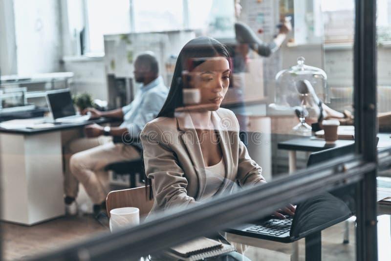 Сконцентрированный на работе Современная молодая женщина используя компьютер пока wo стоковое фото rf