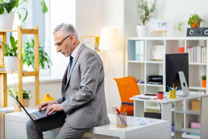 Сконцентрированный серьезный старший человек общаясь с почтовым ящиком стоковое фото rf
