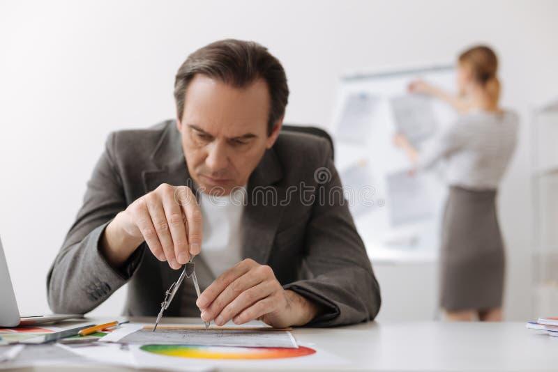Сконцентрированный серьезный чертеж инженера в офисе стоковое фото