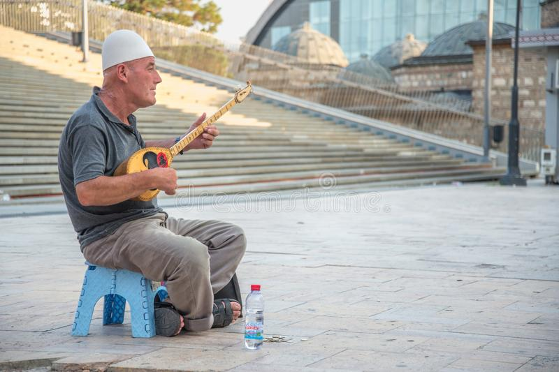 СКОПЬЕ, MACEDONIA-AUGUST 29,2018: человек играет музыку на традиционной зашнурованной аппаратуре, стоковые изображения