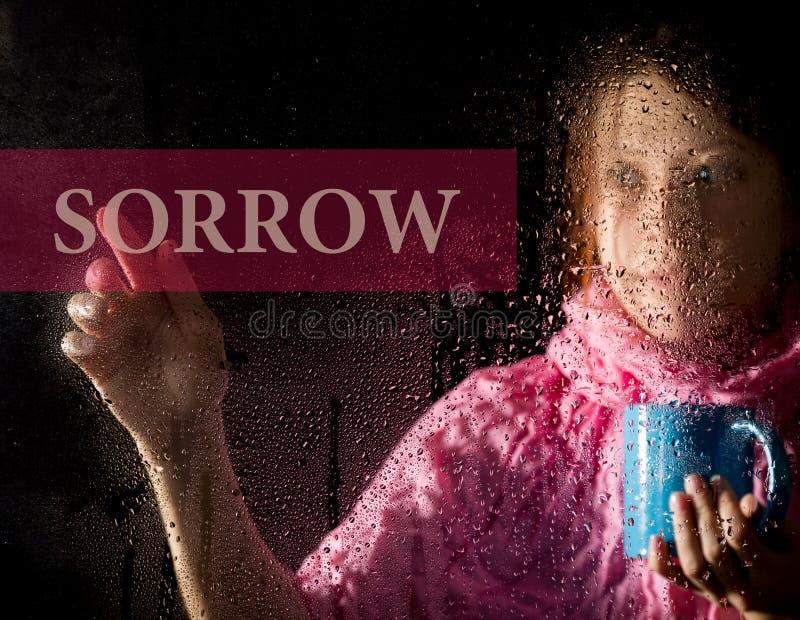 Скорба написанная на виртуальном экране тоска молодой женщины и унылое на окне в дожде, она держа чашку горячего стоковое изображение