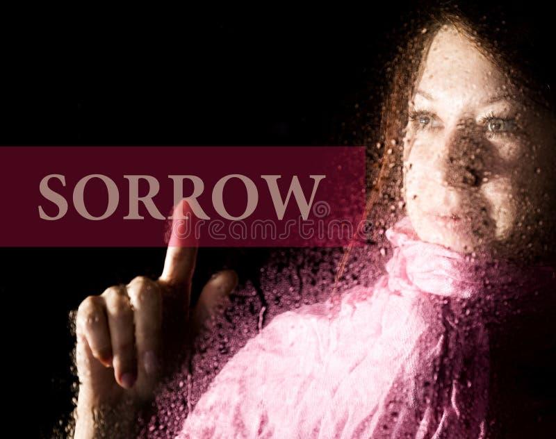 Скорба написанная на виртуальном экране тоска молодой женщины и унылое на окне в дожде, ее шарфе шеи теплом стоковое фото rf