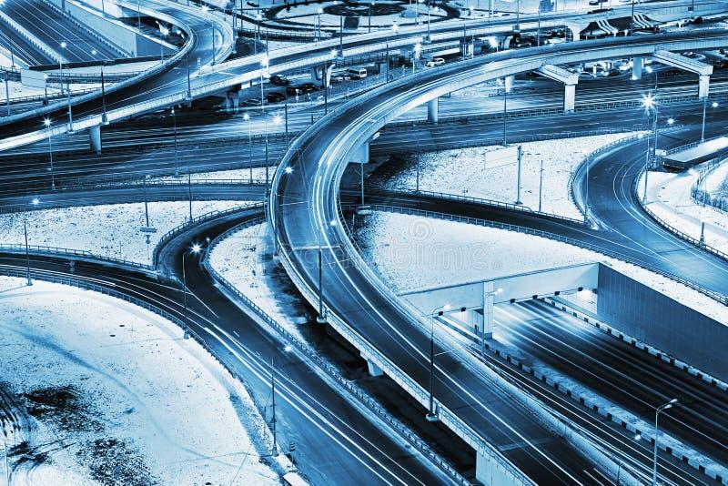 Скоростное шоссе в ноче с автомобилями освещает в современном городе стоковые изображения rf