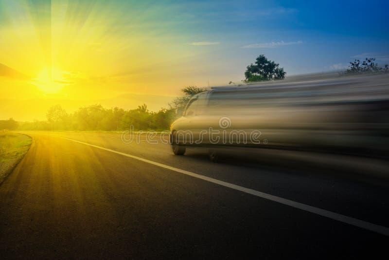 Скорость автомобиля очень быстрая на дороге в вечере и заходе солнца лучей Используя концепцию предпосылки идеи автомобильную стоковое фото rf
