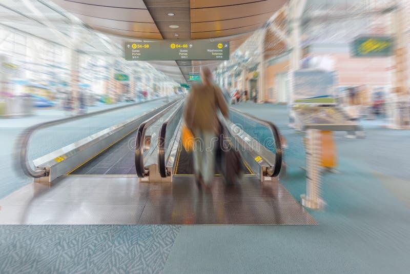 Скорост-прогулка Travelator для пассажиров на авиапорте с silhoue стоковая фотография