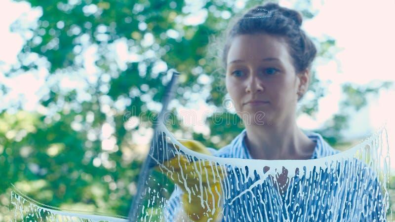 Скребок красивого окна мыть девушки идущий на стекле стоковые изображения rf