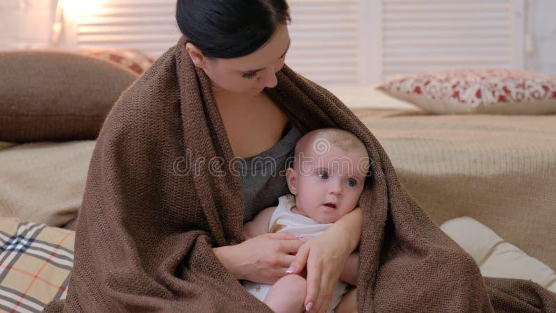 Скрепление ребенка мамы отдыха младенца любящего касания младенческое стоковое изображение