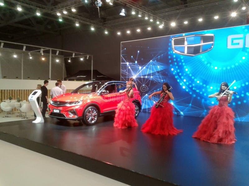 Скрипачи в красных платьях Салон 2018 автомобиля Москвы международный стоковое изображение