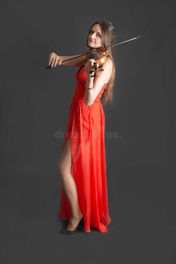 Скрипач в красном платье стоковые изображения rf