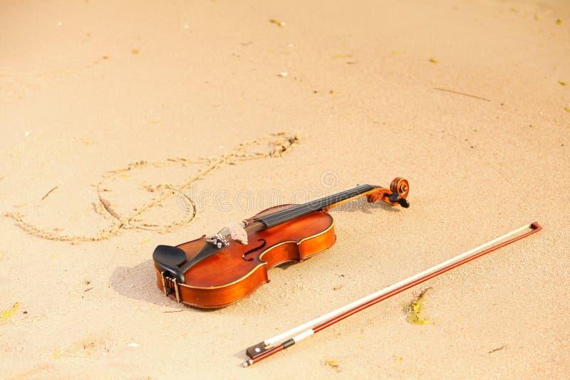 Скрипка и ключ g на пляже. Принципиальная схема музыки стоковые фото