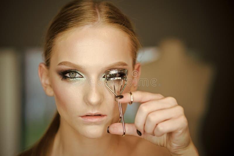 Скручиваемость женщины хлещет с инструментом красоты, взглядом Curler ресницы пользы женщины для состава глаза Модель с курчавыми стоковая фотография