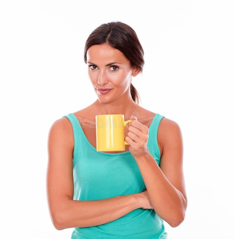 Скрытное усмехаясь брюнет с кружкой кофе стоковая фотография rf
