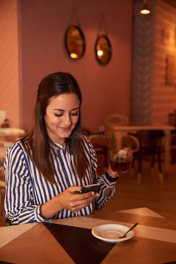 Скрытное millenial в ресторане с телефоном стоковая фотография rf