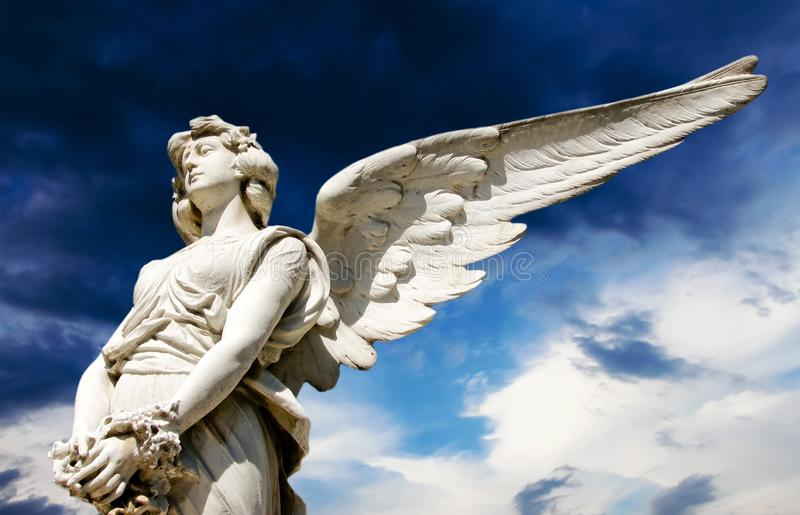 Скульптура ангел-хранителя белая мраморная с открытыми длинными крыльями через рамку против яркого солнечного темно-синего неба с стоковые фото