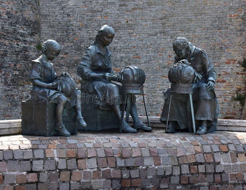 Скульптура в Offida, 3 женщинах делая традиционный шнурок катушкы стоковая фотография rf