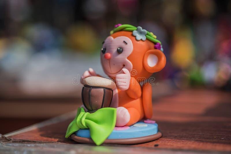 Скульптура глины оранжевокрасной обезьяны барабаня небольшой игрушкой стоковая фотография
