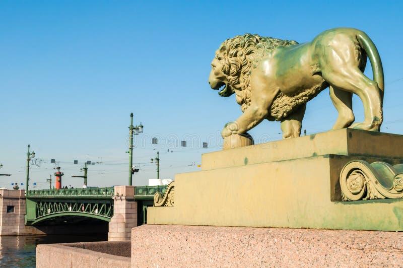 Скульптура льва на обваловке Адмиралитейства против моста дворца в Са стоковые изображения rf