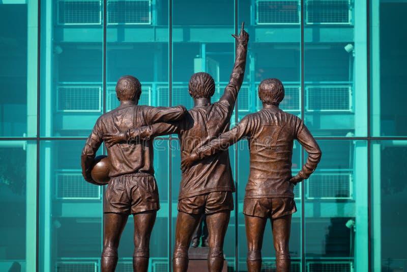 Скульптура объединенной троицы бронзовая на старом стадионе Trafford в Манчестере, Великобритании стоковое изображение rf