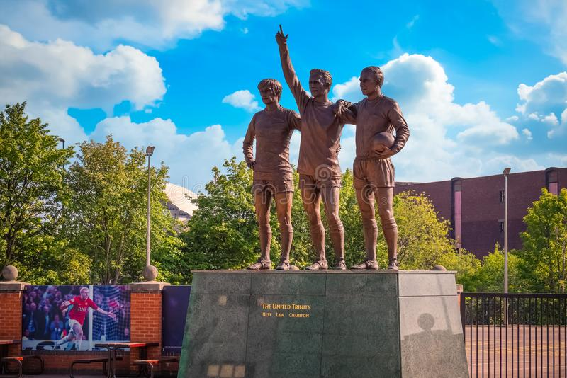 Скульптура объединенной троицы бронзовая на старом стадионе Trafford в Манчестере, Великобритании стоковое фото rf