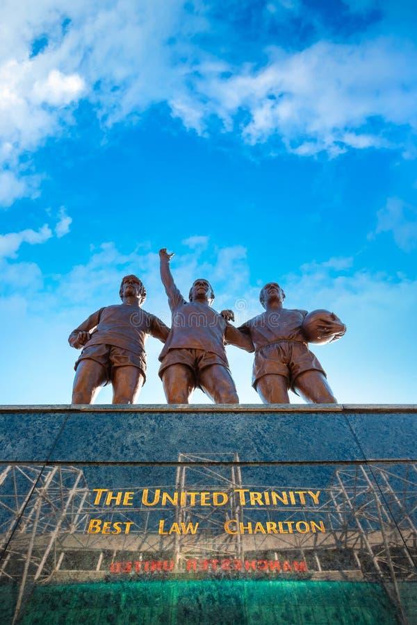 Скульптура объединенной троицы бронзовая на старом стадионе Trafford в Манчестере, Великобритании стоковая фотография rf