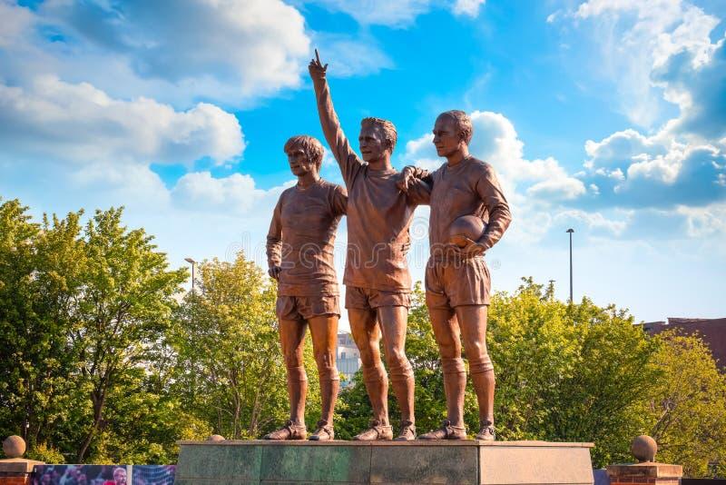 Скульптура объединенной троицы бронзовая на старом стадионе Trafford в Манчестере, Великобритании стоковое фото