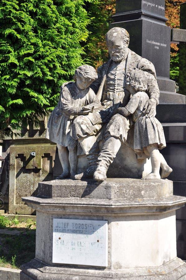 Скульптура человека и детей, кладбища стоковая фотография rf